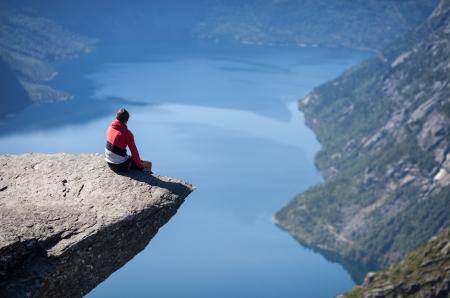 ノルウェーの trolltunga に坐っている人 写真素材