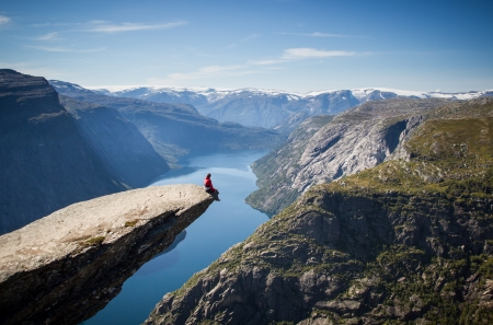 man sitting on trolltunga in norway photo