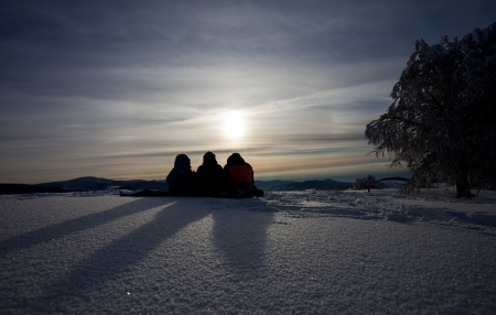 silhouette of friends sitting in snow and enjoying sunset