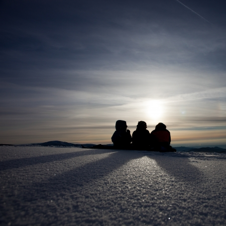 silhouette of friends sitting in snow and enjoying sunset  photo