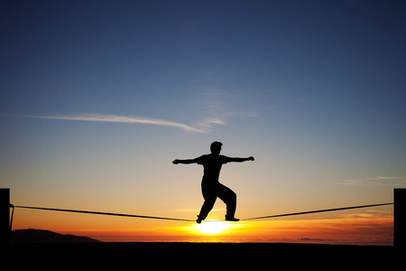 silhouette of slackliner in sunset Фото со стока
