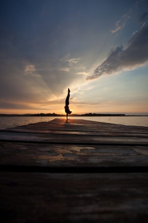 silhouette of gymnast doing a handstand in sunset Фото со стока