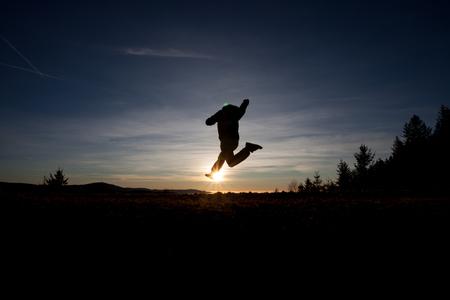 silhouette of man running in sunset photo