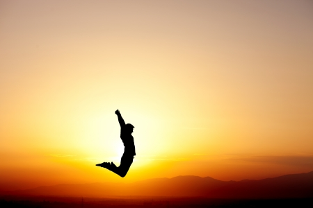silhouette of teen jumping in sunset for fun photo
