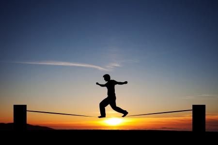 silhouette of man slacklining in sunset photo
