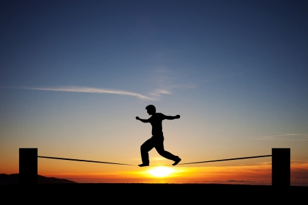 silhouette of man slacklining in sunset Фото со стока
