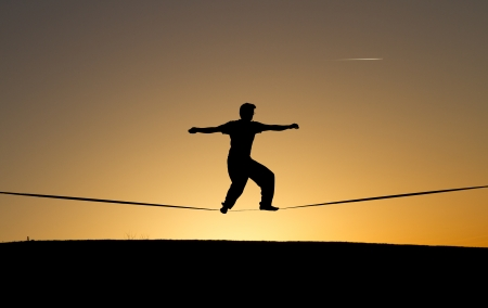 slack: silhouette of man slacklining in sunset Stock Photo