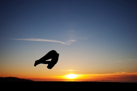 backflip: sunset gymnast doing somersault