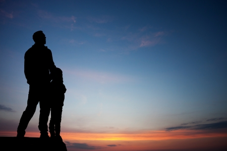 silhouette of father and son in sunset sky photo