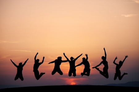 silhouette of kids jumping in sunset 写真素材
