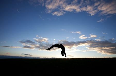 silhouette of gymnast doing back handspring in sunset
