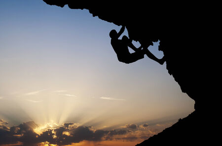 overhanging: silhouette of climber on overhanging rock Stock Photo