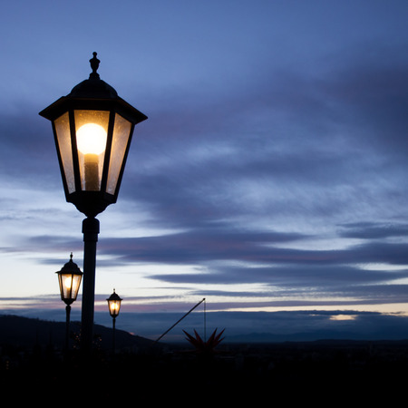 old lamps shining in sunset sky photo