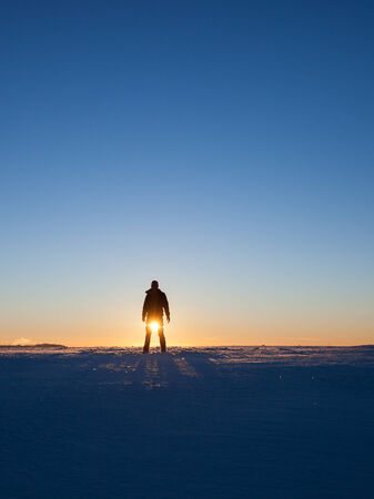 silhouette of man standing in winter landscape photo