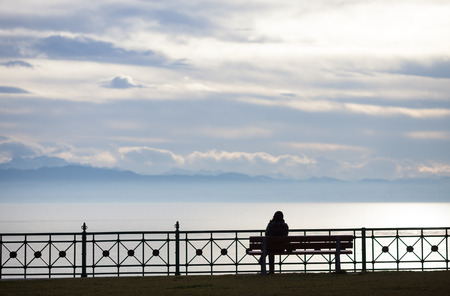friedrichshafen: silhouetted woman sitting on bench at lake constance Stock Photo