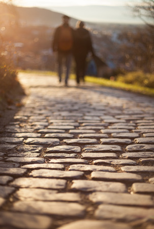 couple walking on cobblestone foot path