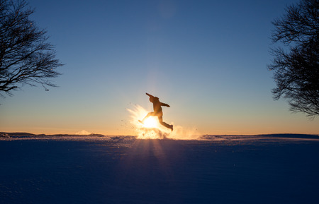 silhouette of man running in winter landscape photo