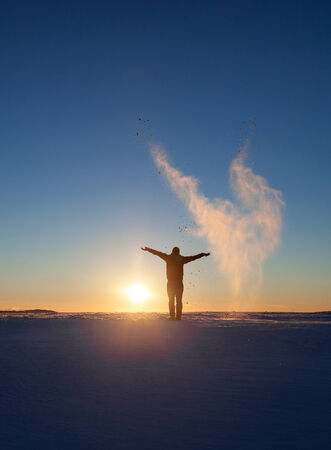 silhouette of man standing in winter landscape and throwing snow photo
