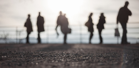blurred silhouettes of people standing in bright sky