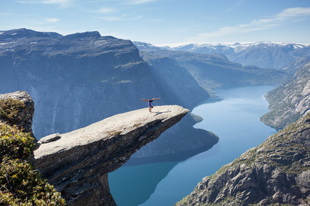 female gymnast doing a handstand on trolltunga rock in norway photo