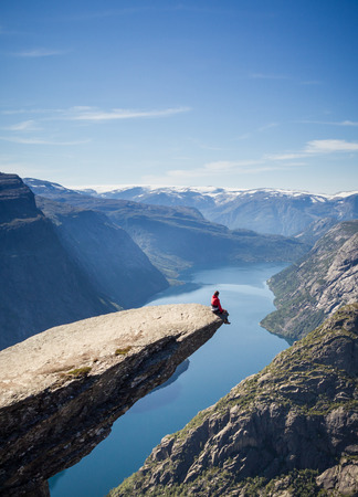 ノルウェーの trolltunga 岩の上に座っている男