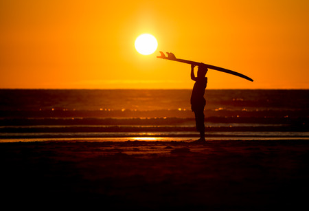 watersport: silhouetted man with surfboard in sunset at beach