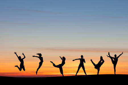 silhouetted group tumbling and dancing in sunset Stock Photo