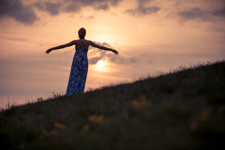 spreading arms: woman on hill enjoying sunset and spreading arms