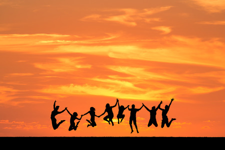 silhouetted friends jumping in sunset