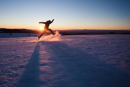 silhouetted man running through snow in winter landscape Stockfoto