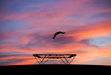 silhouette of man on trampoline in sunset Фото со стока