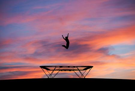 silhouette homme sautant sur le trampoline dans le coucher du soleil Banque d'images