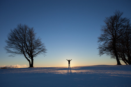 evening glow: silhouetted man standing in winter landscape
