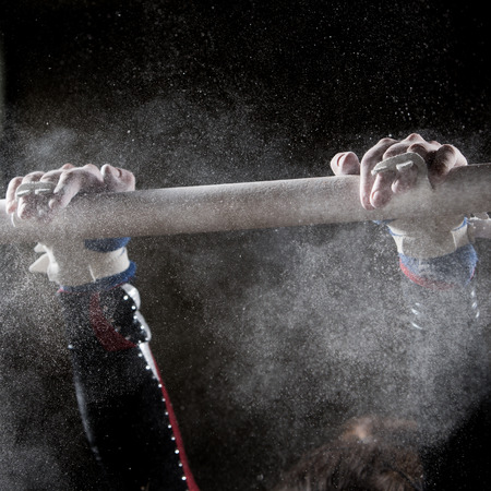 uneven: hands of gymnast with chalk on uneven bars