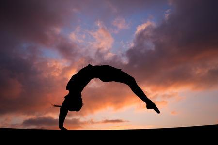 夕焼け空の女性体操選手のハンドをバックアップします。 写真素材