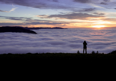 silhouetted photographer standing above fog on hill Фото со стока