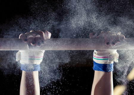 gymnastics sports: hands of gymnast with chalk on uneven bars