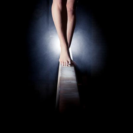 balanza: pies del gimnasta en barra de equilibrio Foto de archivo