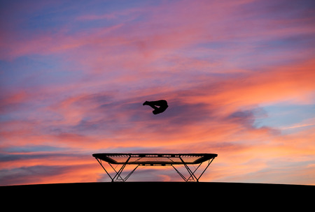 somersault: silhouette of man on trampoline in sunset Stock Photo