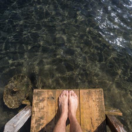 pies masculinos: los pies en el muelle de madera