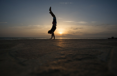 handstand: silhouetted man doing handstand in sunset Stock Photo