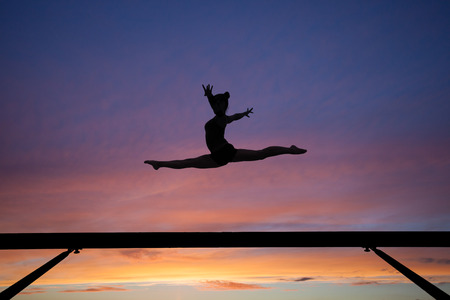 the splits jump on balance beam in sunset