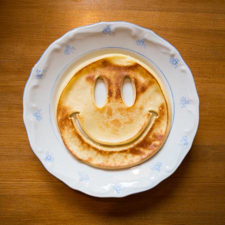 caras graciosas: sonriendo panqueque en un plato Foto de archivo