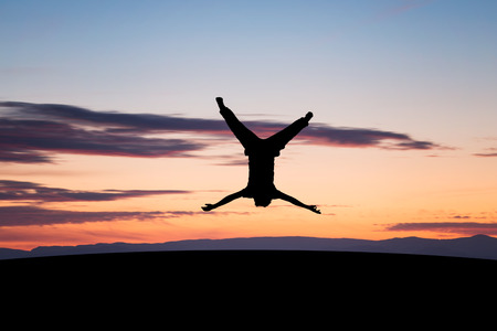 BACKFLIP: silhouetted young man jumping upside down in sunset