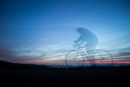 cyclist in motion blur in blue sky Stock Photo