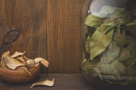 dried mushrooms and spices of bay leaf on a wooden background  dried mushrooms and spices of bay leaf in rural style. Stock Photo
