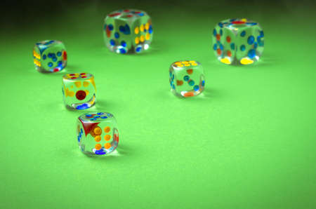 Cubes of casino on green cloth  transparent cubes on green cloth