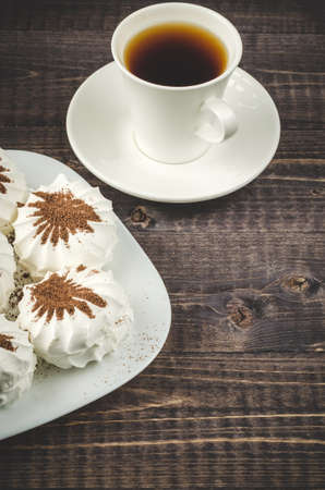White marshmallows and cup of coffee on a wooden background  white zephyr marshmallows and white cup with coffee Stock Photo