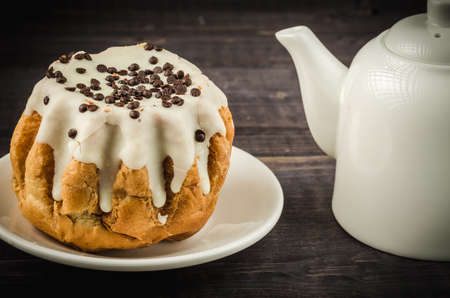 cake in glazes and a white teapotcake in glazes and a white teapot on a dark background Stock Photo