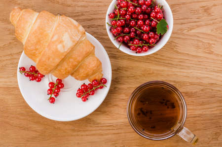 croissant with red berries and a glass of teacroissant with red berries and a glass of tea. Top view
